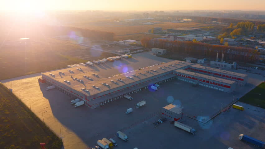 Aerial circling view of logistics center with warehouse, loading hub with many semi-trailers truck load/unload goods at sunset