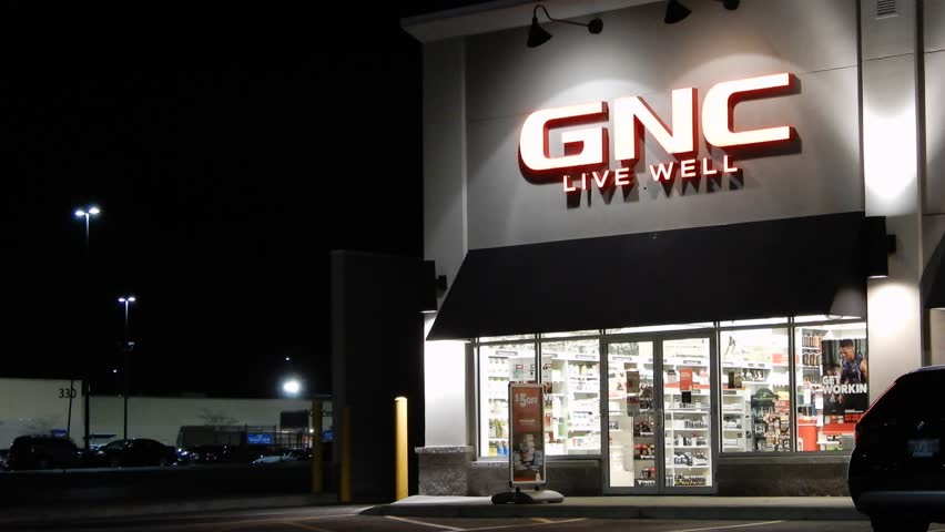 Toronto, Ontario / Canada - 10 30 2017: 4K GNC Store Front With Logo At Night With Cars Parked In Parking Lot
