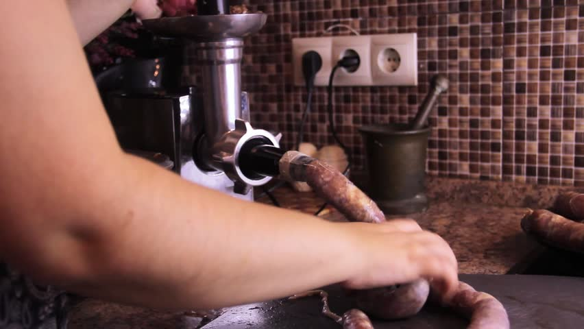 How to make sausage links with meat grinder. Woman use kitchenaid electric meat grinder. keto diet sausages from minced mince and pieces of meat in a natural casing