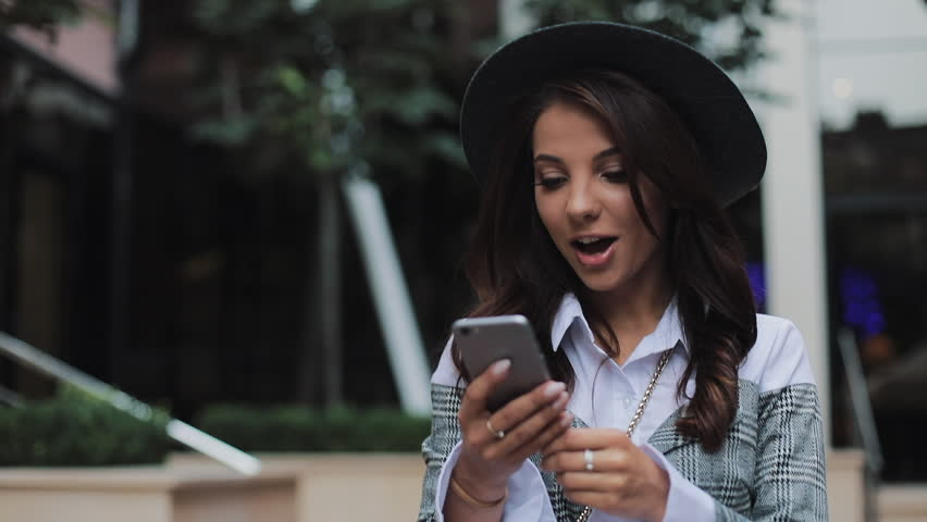Happy young businesswoman walking on urban street using smartphone. Concept: new business, communication, banker. Outside, slow motion | Shutterstock HD Video #1021397920