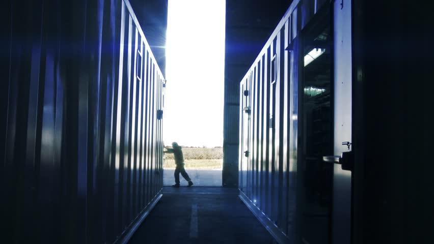 Warehouse Worker opening Metal Door. The Sun shining in the Background.  | Shutterstock HD Video #1021399225