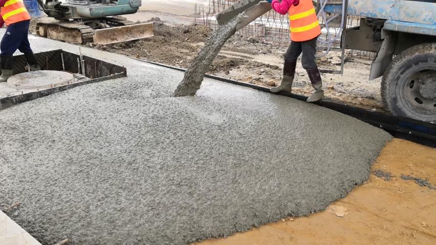 Pouring concrete from a concrete mixer. Man working with concrete mixer.Pouring concrete mix on concreting formwork.