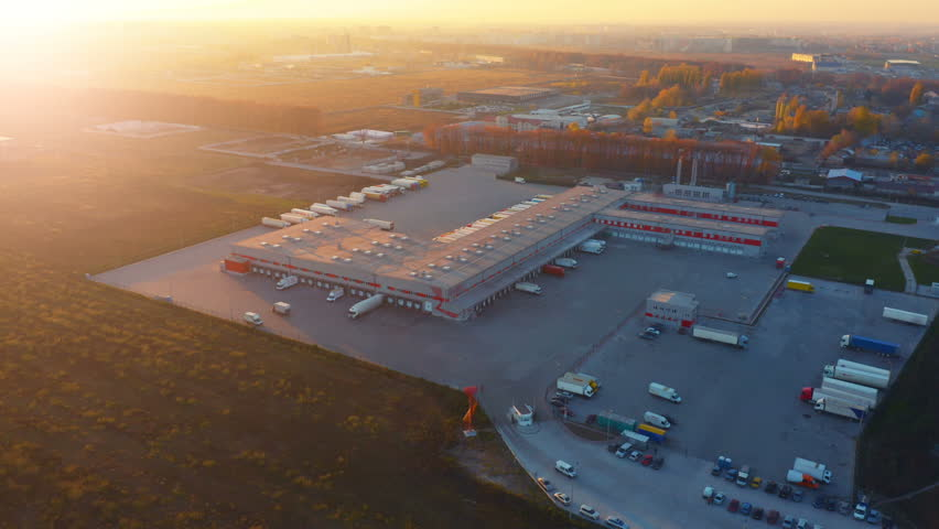 Aerial view of logistics center with warehouse, loading hub with many semi-trailers truck load/unload goods at sunset | Shutterstock HD Video #1021403221