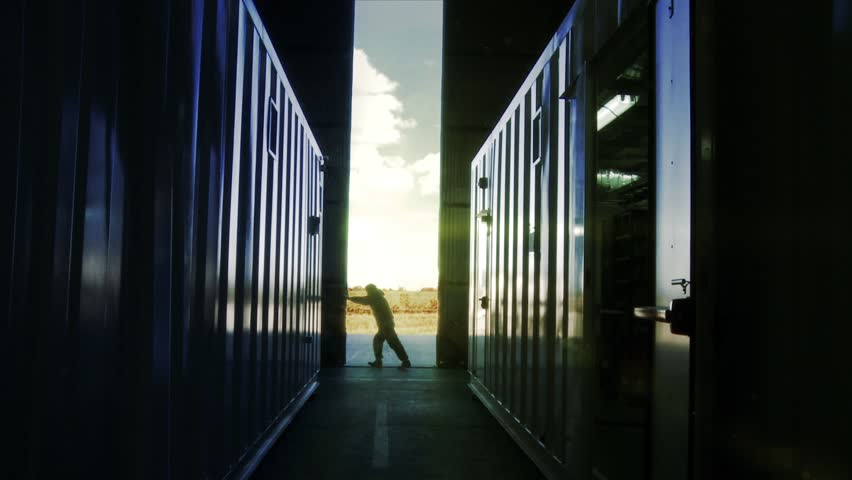 Warehouse Worker opening Metal Gate of a Warehouse with Data Center Racks and Telecommunications Equipments in Containers Inside. Royalty-Free Stock Footage #1021422193