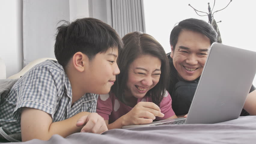 Happy family Father mother and son watching on laptop computer and having fun, Slow motion 4K  asian family rest on bed with laptop computer #1021435987