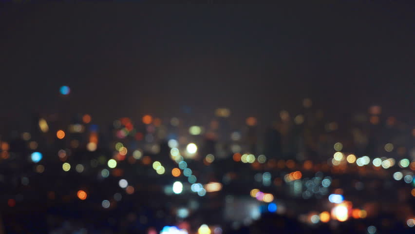 Bokeh background of skyscraper buildings in city with lights, Blurry photo at night time. 4K cityscape