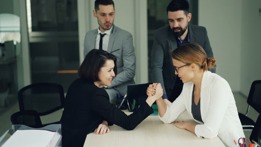 Pretty young women are competing in arm wrestling in office during break while guys are watching and laughing. Corporate culture, fun and youth concept.