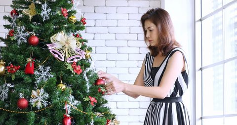 Close up scene Video of Asian woman in black and white dress is decorated huge Christmas tree by ball ornamental, she stand beside window, white bricks wall is Background, Christmas theme.