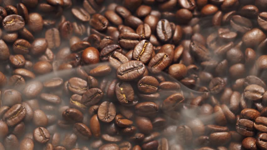 Fragrant coffee beans are roasted in a frying pan, smoke comes from coffee beans. The whole composition scrolls slowly around the camera.  | Shutterstock HD Video #1021452334
