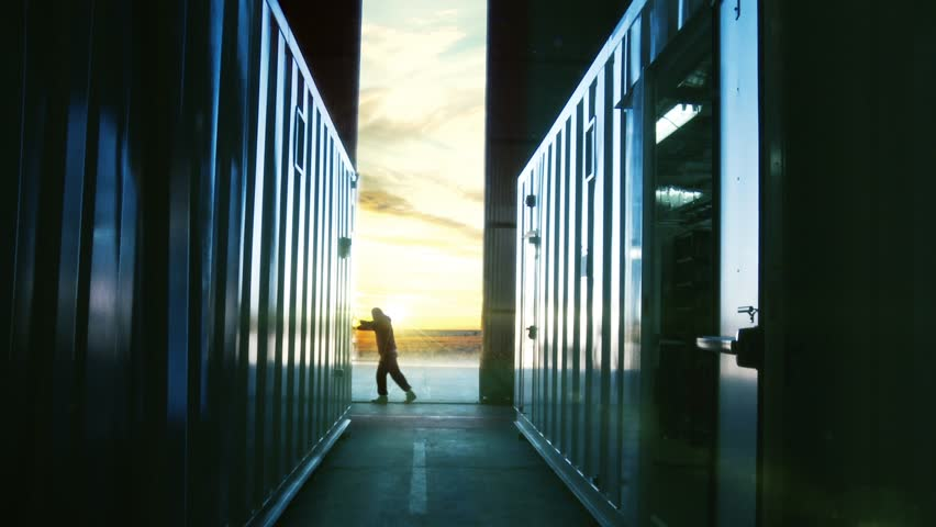 Man Opening Door of a Container Warehouse at Dusk. Orange Sky in the Background.  #1021461178