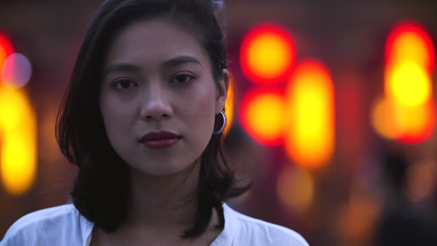 Close up of one beautiful young asian girl looking at camera smile at urban summer evening, wind blowing her hair, people walking in the background with red lantern slow motion