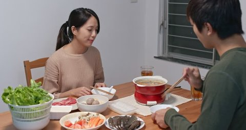 Chinese couple having hot pot at home