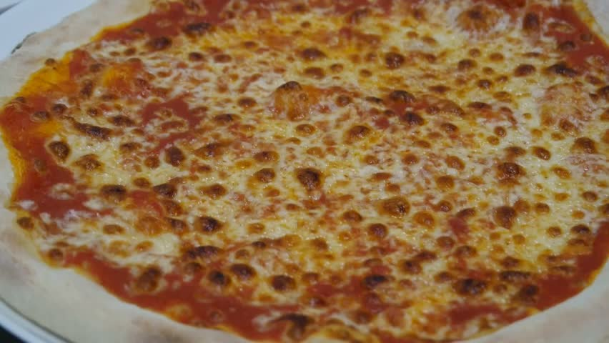 Cooked  pizza is cut with a round pizza knife closeup. Inside italian pizzeria, process of preparing perfect pizza #1021475050