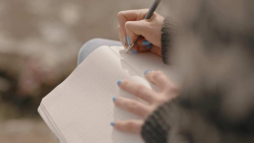 Close up hands woman writing in diary journal teenage girl expressing lonely thoughts on seaside beach