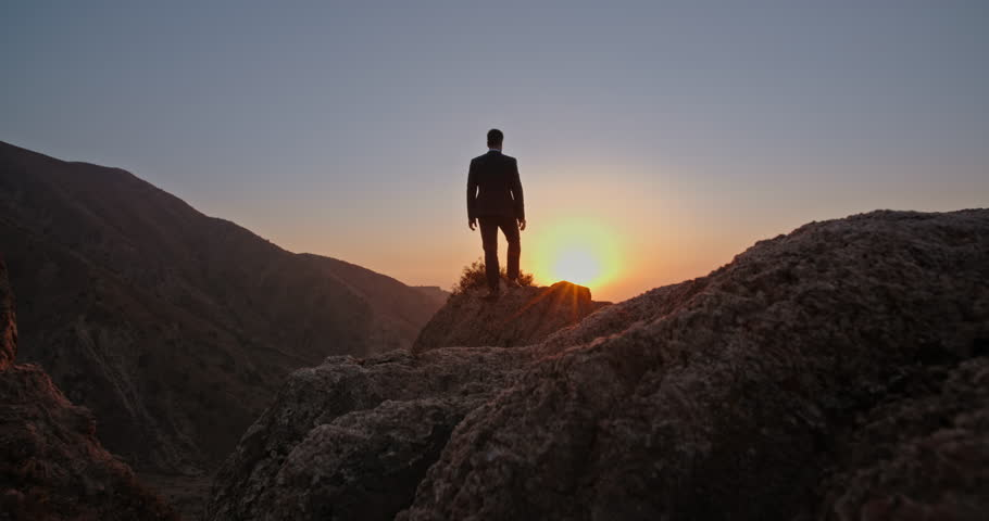 Young successful bsinessman wearing suit and tie standing on top of a mountain, raising his hands - way to success, on top of the world concept 4k #1021483621