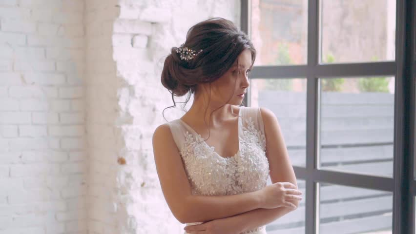 Girl in a light white luxurious wedding dress poses, stands alone in a spacious room, the interior is in a Scandinavian loft, the brunette braided her dark hair in a gentle hairstyle, soft makeup | Shutterstock HD Video #1021484584