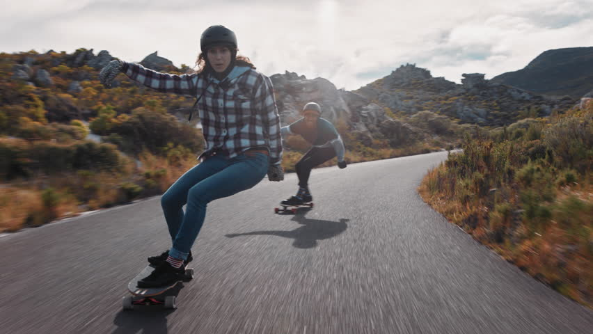 Young happy woman riding longboard friends skating enjoying cruising downhill on beautiful countryside road having fun using skateboard wearing protective helmet