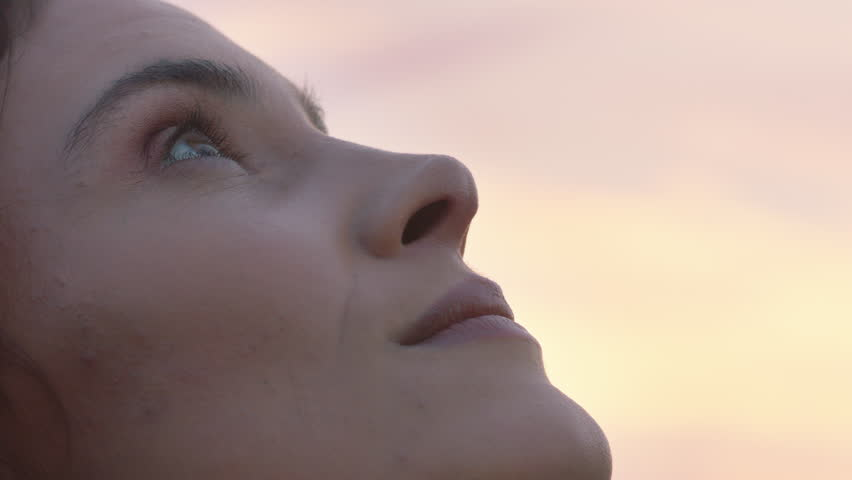 close up portrait of beautiful woman exploring spirituality looking up praying contemplating journey with wind blowing hair in countryside enjoying peaceful sunset #1021487002
