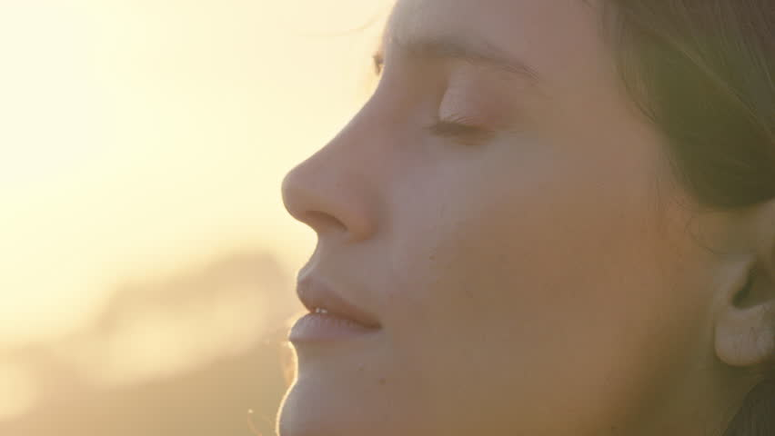 close up portrait of beautiful woman enjoying peaceful sunset exploring spirituality looking up praying contemplating journey with wind blowing hair Royalty-Free Stock Footage #1021487026