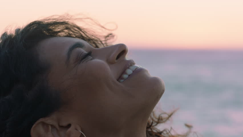 close up portrait of beautiful hispanic woman looking up exploring mindfulness contemplating spirituality with wind blowing hair enjoying peaceful seaside at sunset Royalty-Free Stock Footage #1021487332