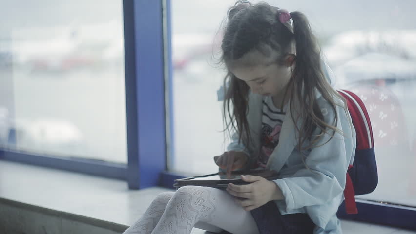 A little girl at the airport at the window uses a tablet #1021489456