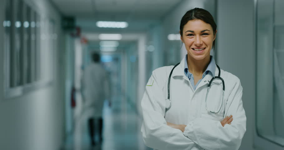 Portrait of smiling female doctor satisfied with her job in a corridor of a hospital. Concept of medicine, technology, health care and people, hospital
