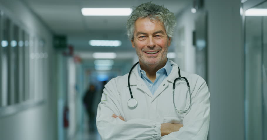 Portrait of smiling male doctor satisfied with his job in a corridor of a hospital. Concept of medicine, technology, health care and people, hospital