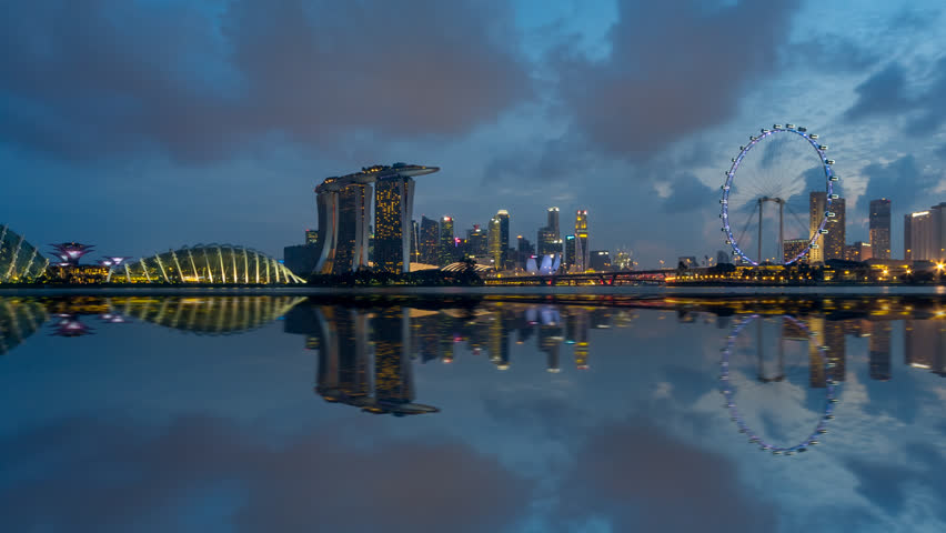 Beautiful Time lapse of Day to Night of Singapore skyline from afar with reflection. Prores. Pan right motion timelapse. 4K available.