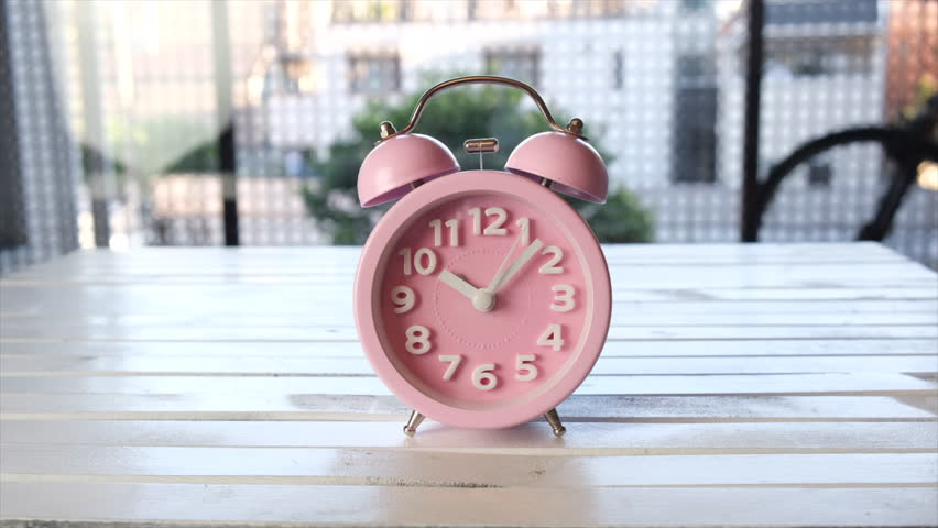 Pink alarm clock on wooden board. Tracking shot. | Shutterstock HD Video #1021538827