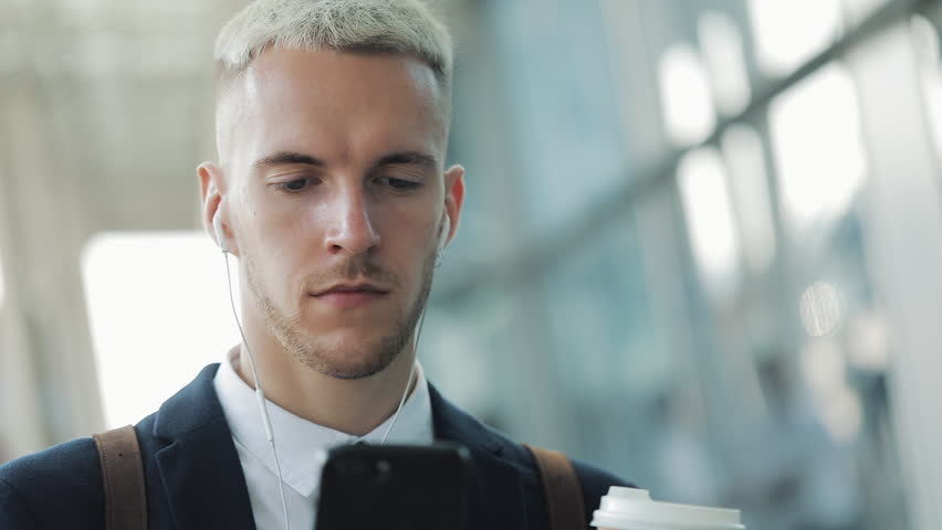 Young businessman standing near office building using smartphone with headphones and drinking coffee. Business man in fashion black suit | Shutterstock HD Video #1021540240