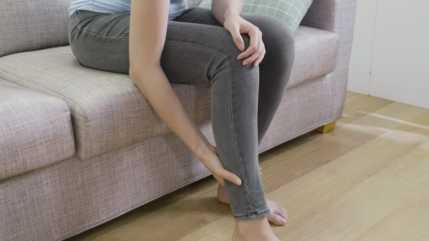 Cramps in leg calves or sprain calf on young asian woman sitting at home resting. overwork injury concept with housewife. unrecognized lady sitting on couch massage her legs. | Shutterstock HD Video #1021546171