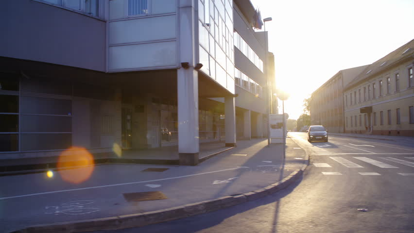 Car side window view of sunset shine on city street HD. Wide shot of side street with sunset in background shining all over the surface. | Shutterstock HD Video #1021557826