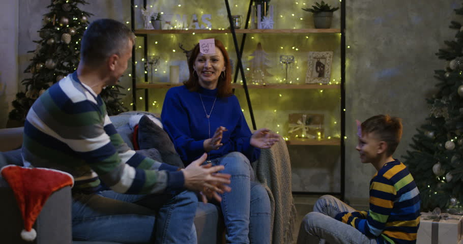 Slow motion shot of a family playing Who am I at Christmas eve   Shutterstock HD Video #1021557898