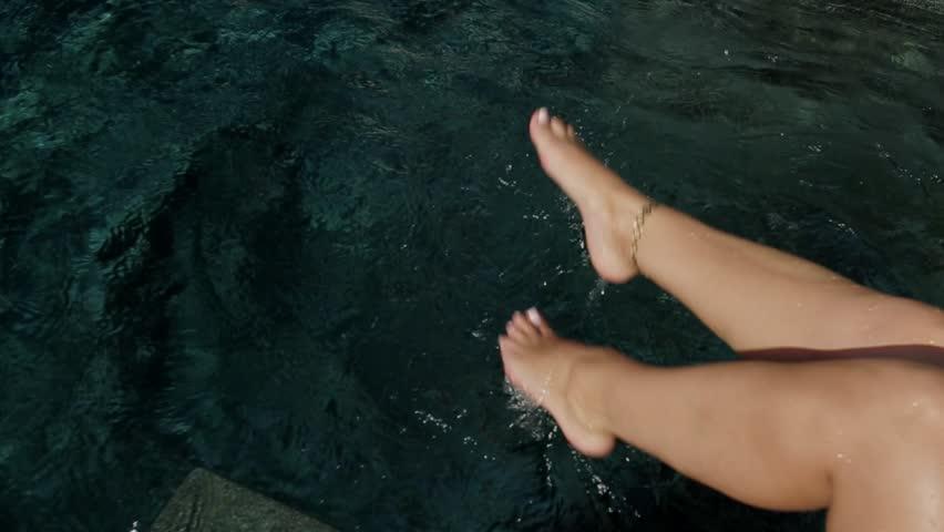 Beautiful slim tanned female legs splashing water in the pool   Shutterstock HD Video #1021565533