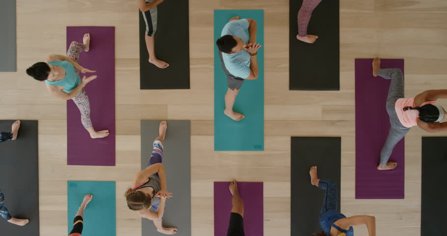 Top view yoga class of young healthy people practicing triangle pose stretching enjoying fitness lifestyle exercising in studio | Shutterstock HD Video #1021566160