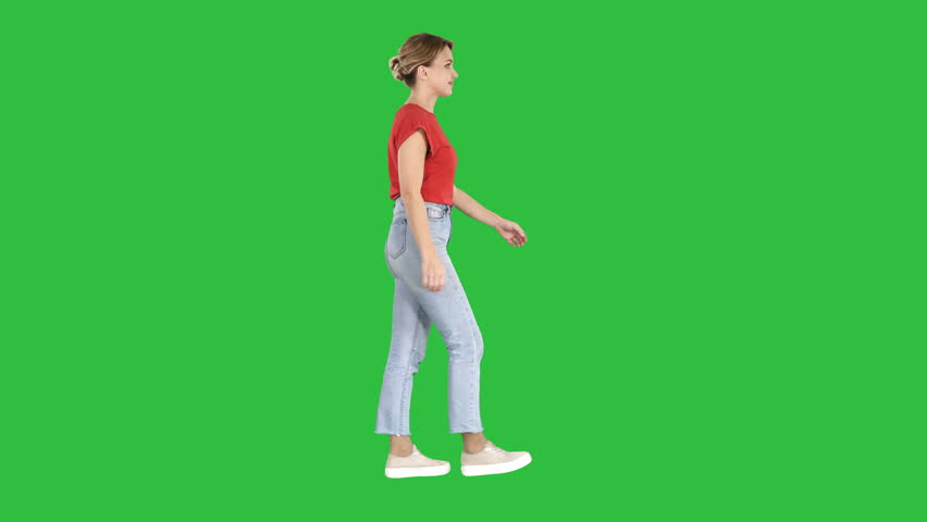Woman in red t-shirt, jeans and sneakers walking on a Green Screen, Chroma Key.