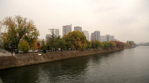 Paris, France - October 2015 : Wide shot of the Ile aux Cygnes, isle of the Swans, in Paris France on an autumn day, with green yellow and orange fall leaves on the trees and buildings of Beaugrenelle