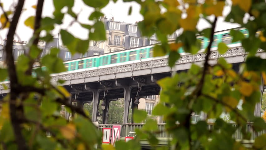 Paris, France - October 2015 : Metro passing on the Bir Hakeim bridge near the Ile aux Cygnes, isle of the Swans, in Paris France on an autumn day, with green yellow fall leaves on the trees