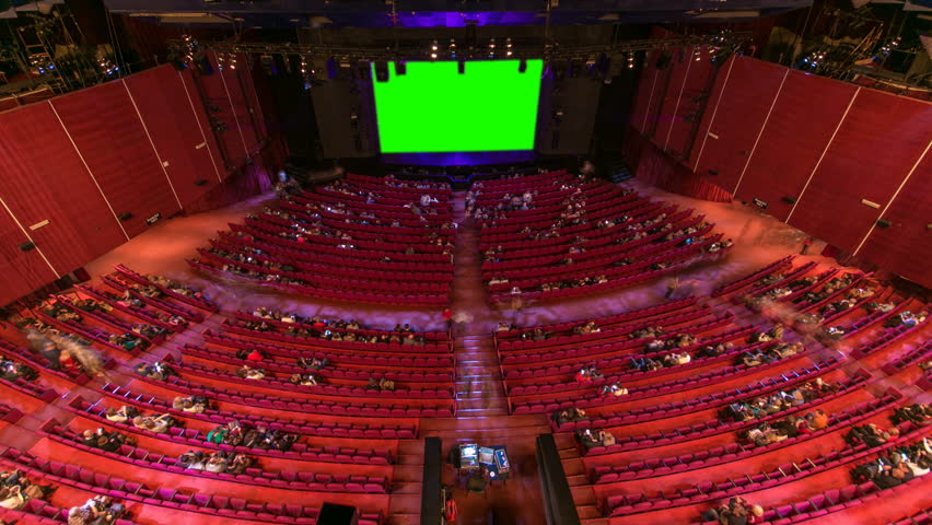 Cinema movie theater auditorium with viewers, red chairs and green projection screen timelapse. People filling empty hall and sitting down to their places very fast