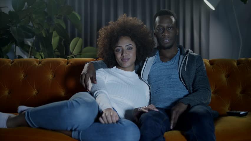 Couple enjoying a cozy night in on the sofa watching tv | Shutterstock HD Video #1021603699