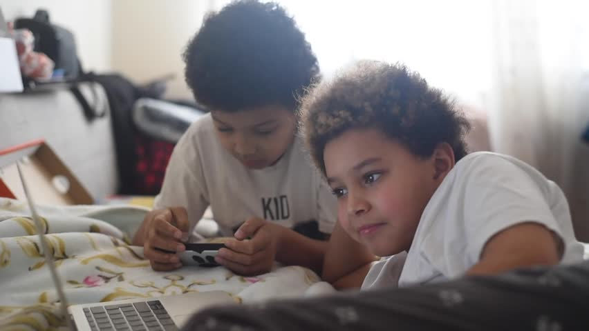 Two cute african american mixed kids using a different gadgets on the bad.  Boy using a laptop to watch a vlog and his twin brother using a mobile phone.  Children and devices. Home schooling. Study  | Shutterstock HD Video #1021640323