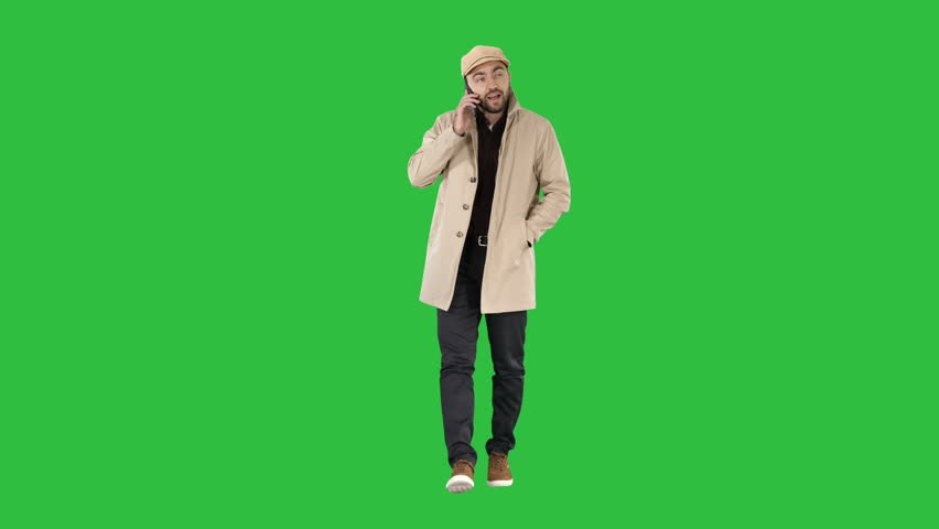 Man in trench coat walking and talking on the phone on a Green Screen, Chroma Key.