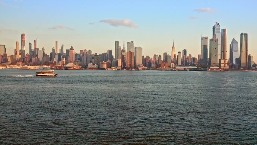 Aerial drone footage of New York skyline. The camera flies over Hudson River towards midtown Manhattan, while a boat crosses the frame.   Shutterstock HD Video #1021705552