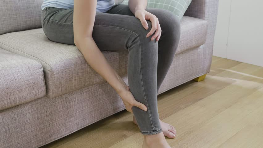 Slow motion unrecognized woman in jeans massage sprain calf sitting in sofa in apartment. young lady having calves cramp pain in leg. female injured painful touching quadriceps and hamstrings muscle | Shutterstock HD Video #1021708438