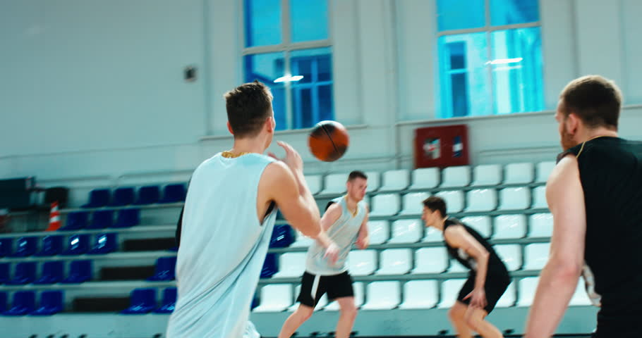 High school team playing basketball indoors, practicing combinations and drills. 4K UHD Royalty-Free Stock Footage #1021722520