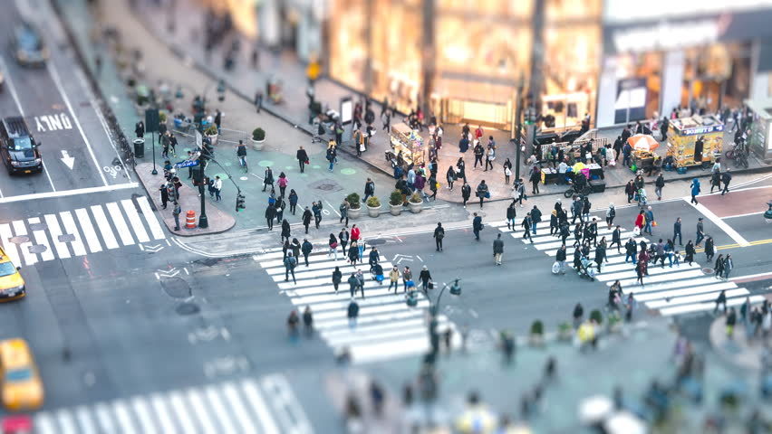 New York City, USA - April 6, 2018: Timelapse, time lapse of high angle, aerial view of NYC Herald Square midtown with crowd of people crossing crosswalk at night with tilt and shift effect