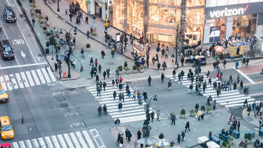 New York City, USA - April 6, 2018: Timelapse, time lapse of high angle, aerial view of building in NYC Herald Square midtown with crowd of people crossing crosswalk, Verizon and H&M store at night