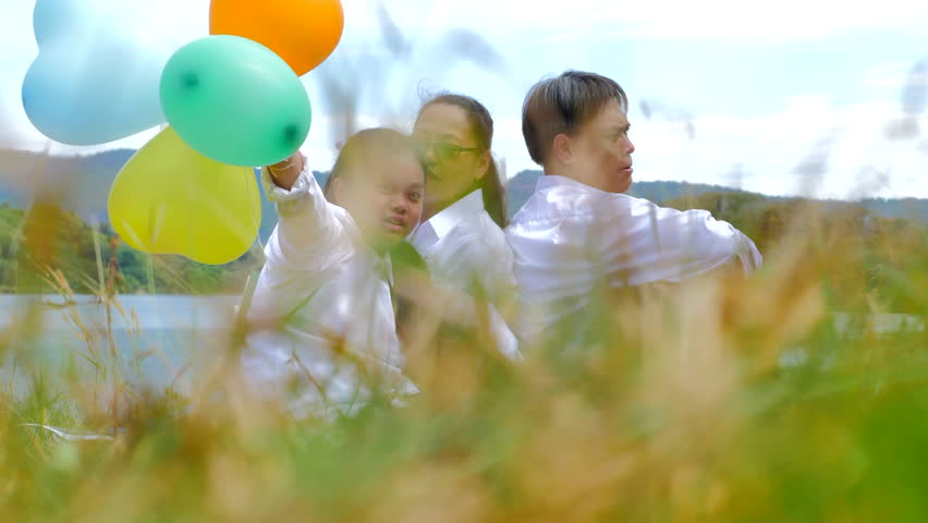 Happy family concept - Asian father playing guitar, mother and Daughter sing a song with colorful balloons , Family having fun together near the lake in the park background the mountain. | Shutterstock HD Video #1021783714