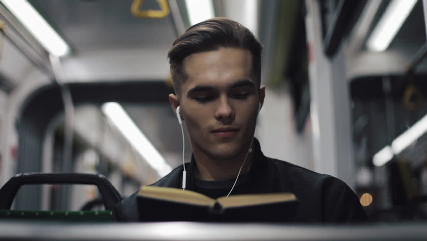 Young handsome man sitting on public transport reading a book - commuter, student, knowledge concept. Young man with headphones in the tram reading a book   Shutterstock HD Video #1021803169