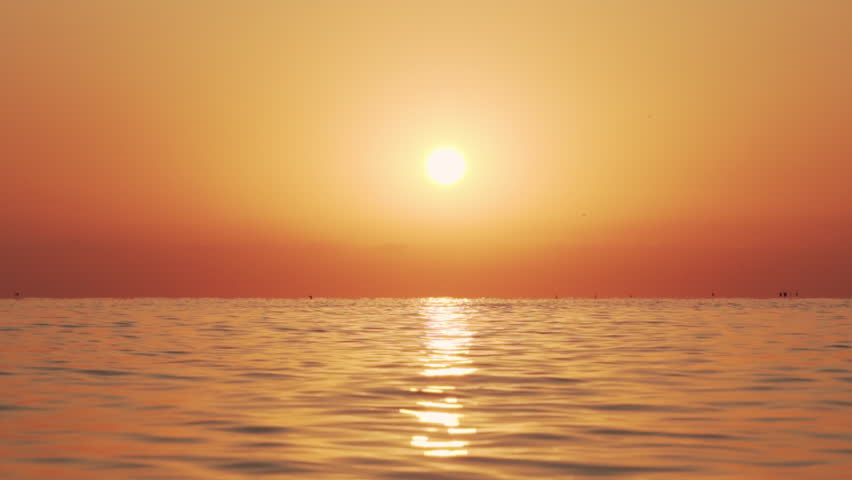 Sea surface small waves against of golden sunrise of sun slow motion. Large disk of sun rises above sea, solar path on water. Golden light of sea panorama. Relax. Nature